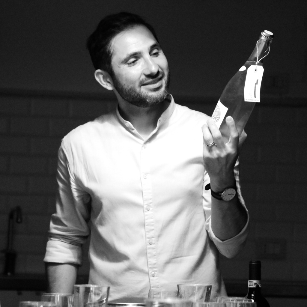 The owner of VinoRoma, Maurizio Di Franco, who is holding a bottle of wine and describing it to members while leading a tasting.