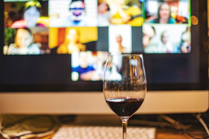 A glass full of red wine in front of a computer screen with a video call with members during a virtual tasting.
