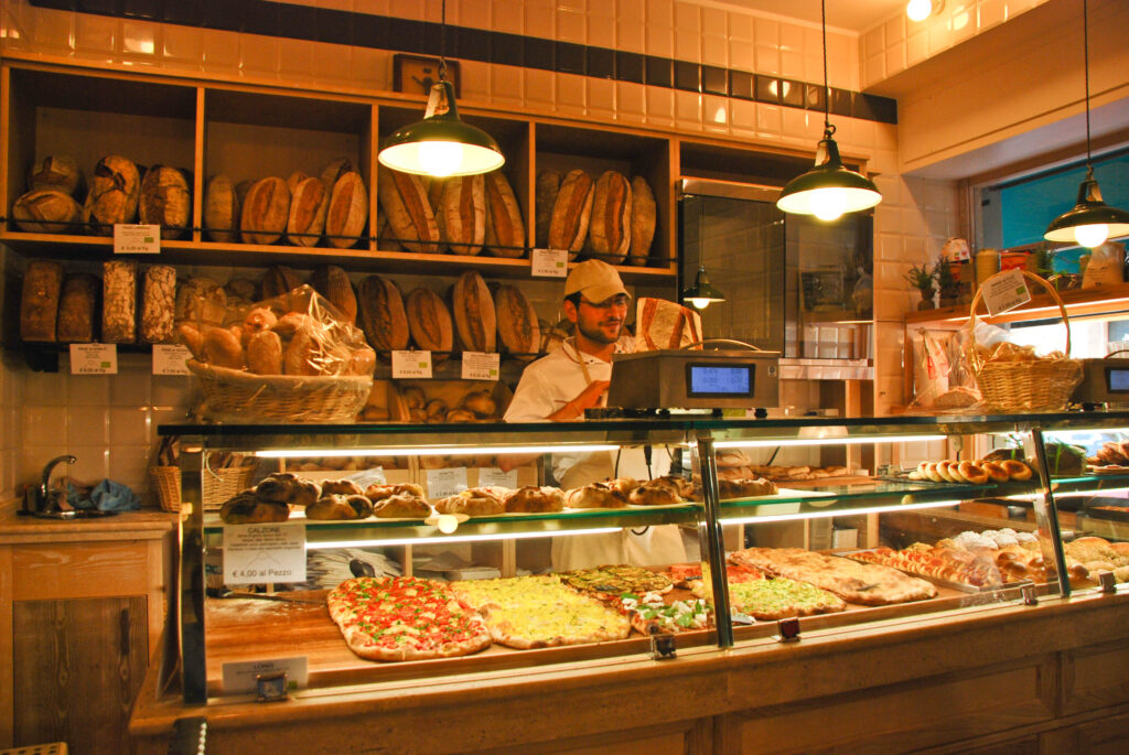 A baker weighing bread behind a counter filled with pizza a soft lighting in a bakery during a walking food tour with members.