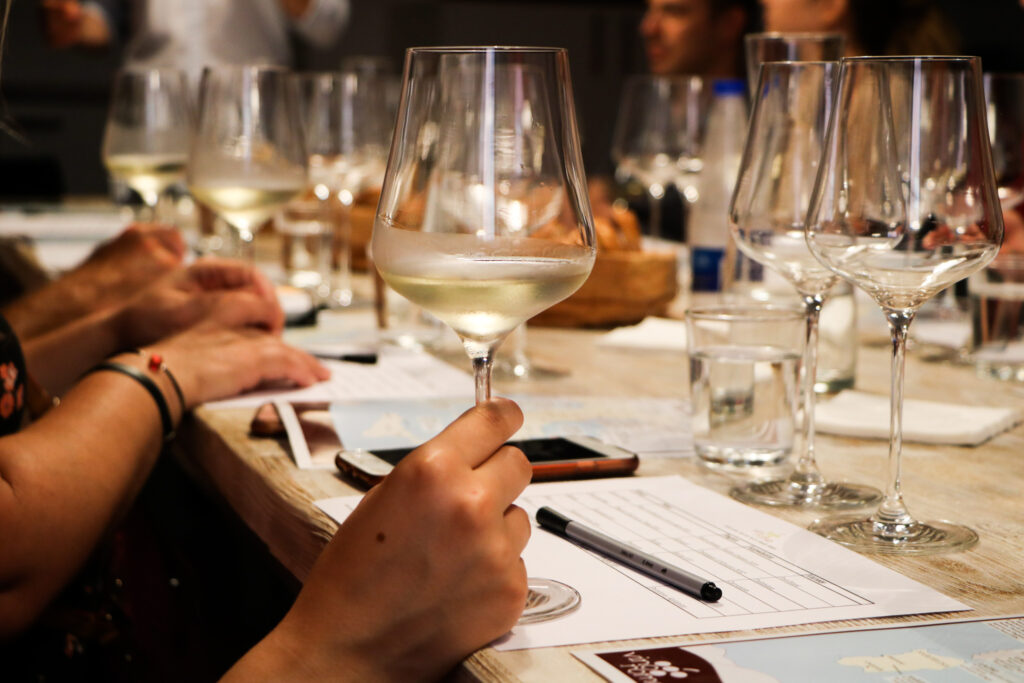 Members at the tasting table of VinoRoma holding glasses full of white wine while learning how to taste wines during a tasting.