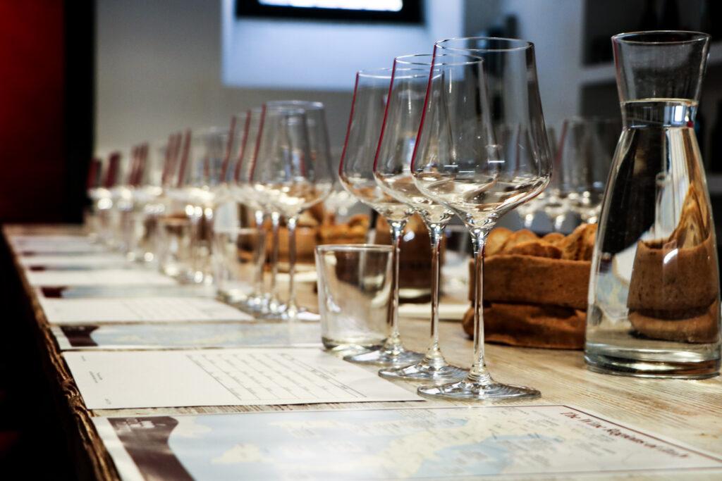 Il tavolo di degustazione di VinoRoma apparecchiato con i bicchieri, acqua, pane e dei materiali importanti per un evento speciale.